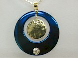 Blued Titanium Circle pendant with a centre dangle gold disk